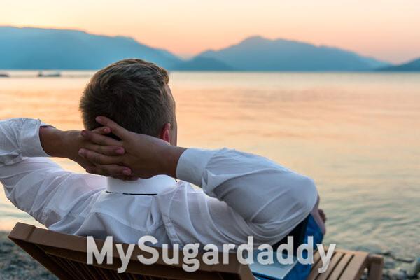 uomo che si rilassa al tramonto in riva al mare