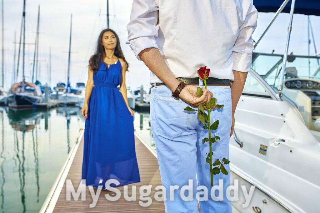 Galateo per Sugar Baby: appuntamento, uomo con rosa rossa e ragazza mora con abito blu
