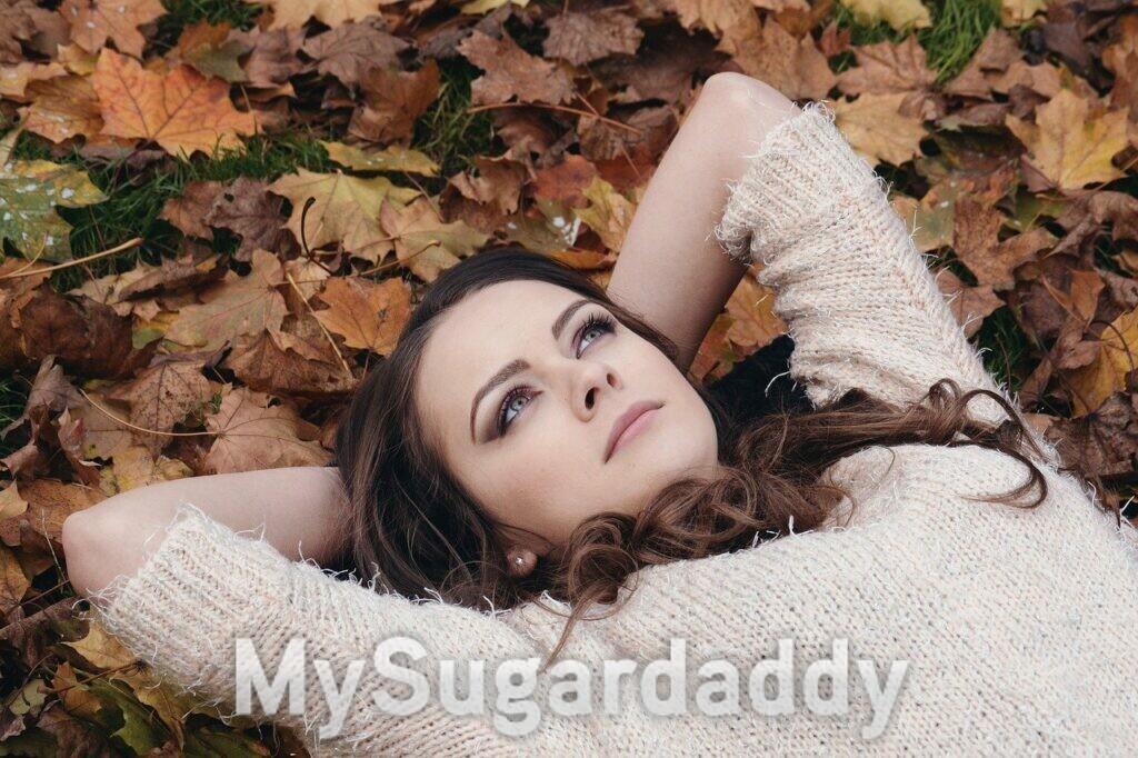 ragazza coricata sulle foglie autunnali che pensa