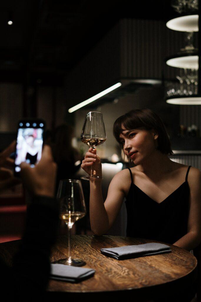 Primo appuntamento - ragazza che fa una foto con vino al ristorante