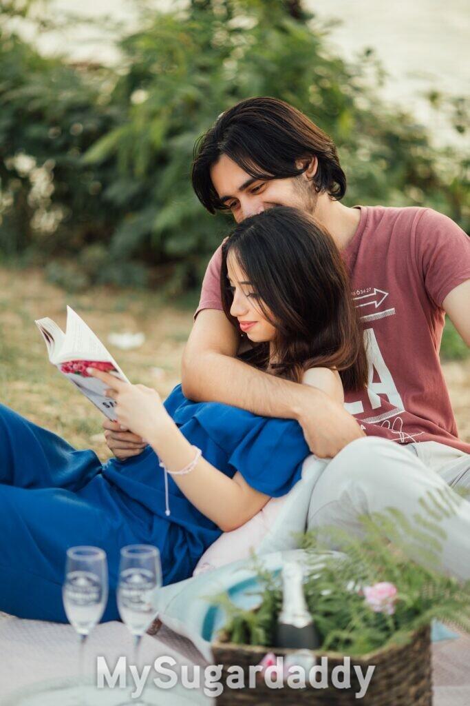 coppia al parco abbracciata - ragazza che legge